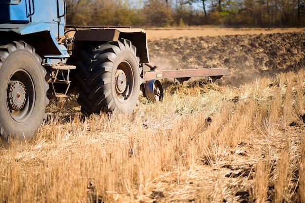 Trator de agricultura azul arar no outono no campo.