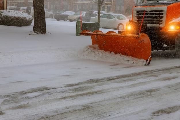 Trator de neve remove a neve durante a queda de neve