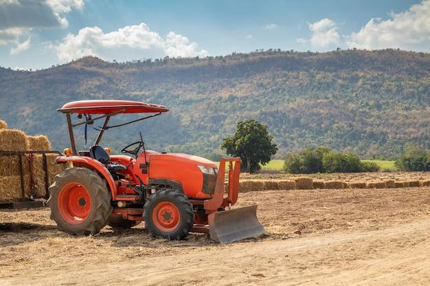 Trator em campo de agricultura com montanha e céu azul