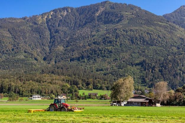 Trator em um campo em uma fazenda de corte de grama para alimentação do gado.