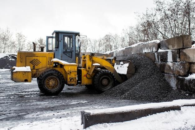 Trator envia balde de carvão.