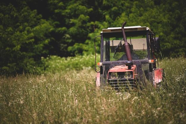 Trator industrial cortando grama em um campo