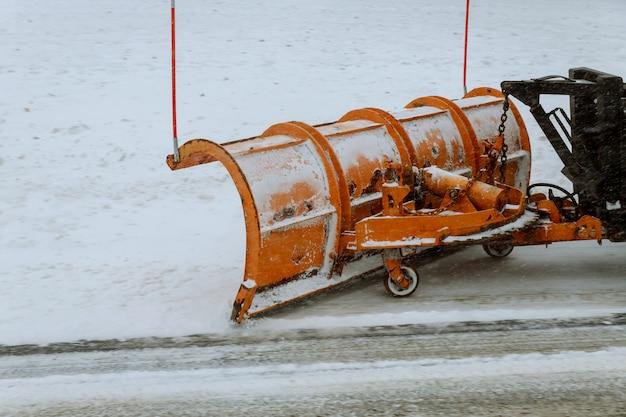 Trator limpa o caminho após a queda de neve pesada.