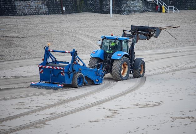 Trator limpando a areia da praia