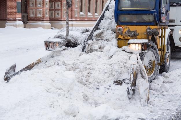 Trator limpando as ruas de grandes quantidades de neve na cidade após uma tempestade de neve.