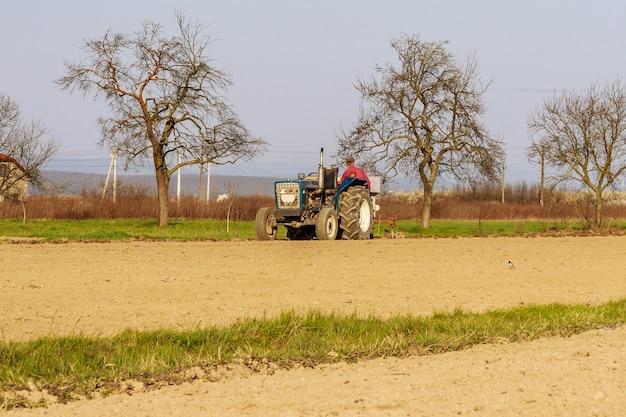 Trator no campo plantando batatas em campos agrícolas férteis