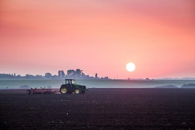 Trator processa o solo no campo