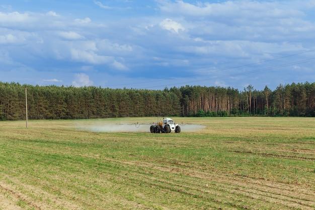Trator pulveriza fertilizantes químicos líquidos em plantações de milho