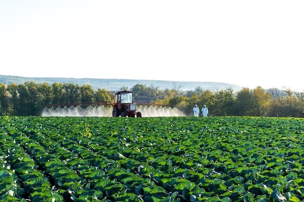 Trator pulveriza produtos químicos e pesticidas em vegetais de campo de fazendas