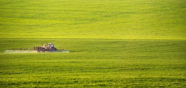 Trator pulverizando pesticidas no campo com pulverizador no verão