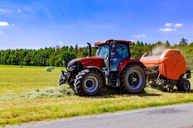 Trator puxando uma grande enfardadeira redonda para coletar ração de grama de um campo de verão. borrão.