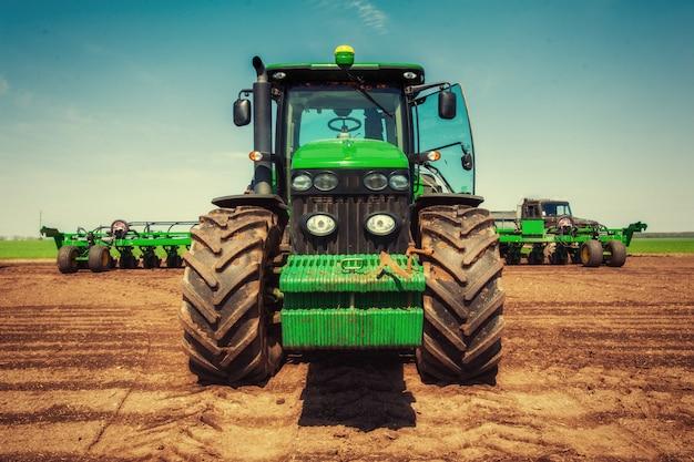 Trator que ara o campo agrícola em preparação para o plantio de primavera
