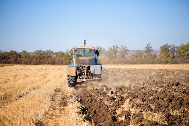 Trator semeando diretamente no restolho após a colheita com céu azul durante o dia de outono.