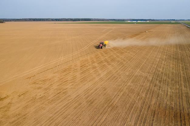 Trator semeia trigo na vista superior do campo