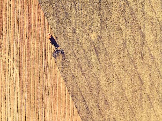 Trator trabalhando nos campos, vista aérea, feno no campo. a vista do topo. o trator colhe grama seca.