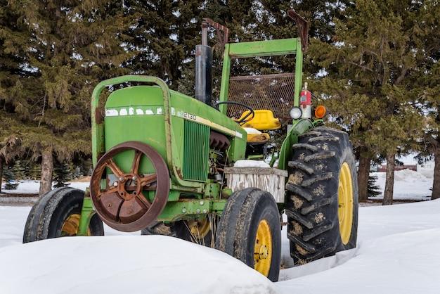 Trator verde e amarelo vintage em uma deriva de neve em saskatchewan, canadá