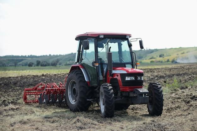 Trator vermelho brandnew no funcionamento de campo. trator cultivando o solo e preparando um campo para o plantio