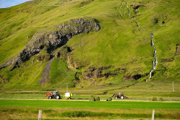 Trator vermelho, coleta de pilha de grama em campo verde com lindo rio passando pela montanha no fundo.