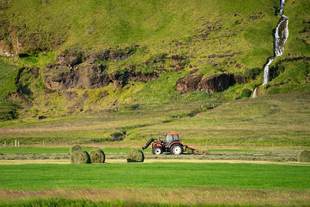 Trator vermelho coletando grama em campo verde com lindo rio passando pela montanha no fundo.