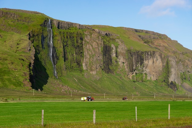 Trator vermelho coletando grama em um campo verde com uma bela cachoeira caindo da montanha