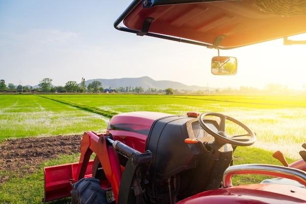 Trator vermelho no campo agrícola em dia ensolarado de verão