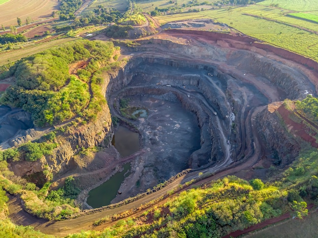 Tratores e caminhões removendo pedras de dentro de um buraco na pedreira