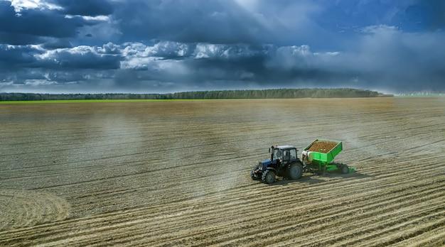 Tratores trabalhando em um campo que cultiva o solo pronto para o plantio das batatas. vista aérea.
