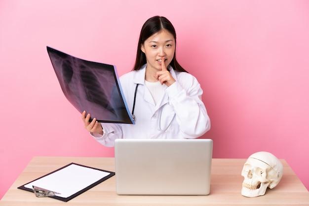 Traumatologista chinês profissional no local de trabalho, fazendo o gesto de silêncio