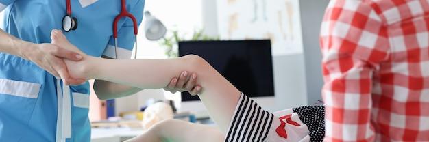 Traumatologista ortopedista examina perna de criança em consultório médico