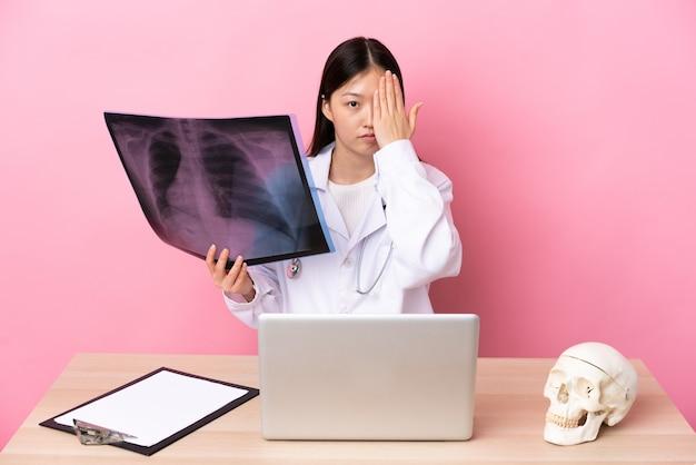 Traumatologista profissional chinês no local de trabalho cobrindo um olho com a mão