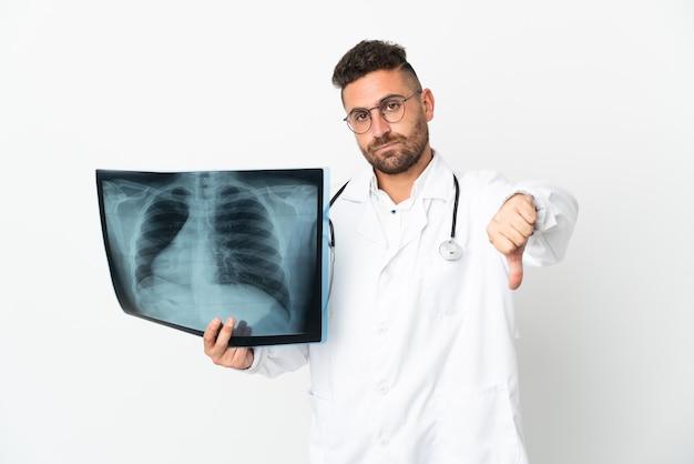 Traumatologista profissional isolado em fundo branco mostrando polegar para baixo com expressão negativa