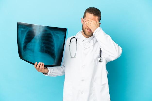 Traumatologista profissional isolado em um fundo azul, cobrindo os olhos com as mãos. não quero ver nada