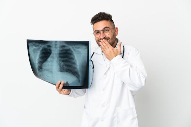 Traumatologista profissional isolado no fundo branco feliz e sorridente cobrindo a boca com a mão