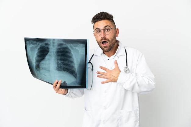 Traumatologista profissional isolado no fundo branco surpreso e chocado ao olhar para a direita