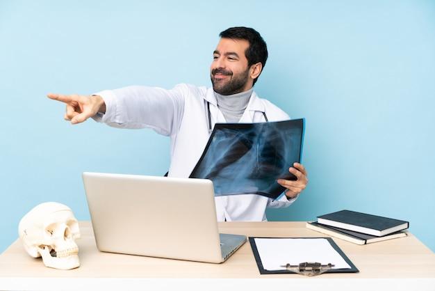 Traumatologista profissional no local de trabalho, apontando o dedo para o lado e apresentando um produto