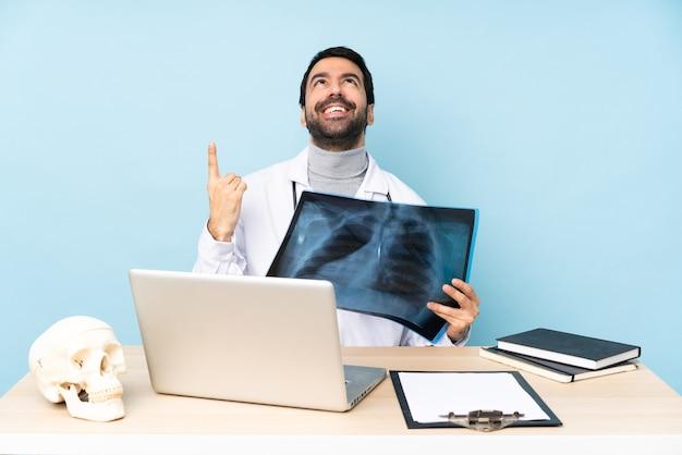 Traumatologista profissional no local de trabalho apontando para cima e surpreso