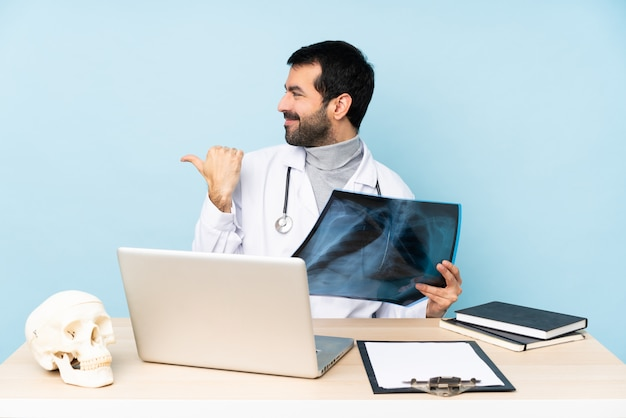 Traumatologista profissional no local de trabalho, apontando para o lado para apresentar um produto