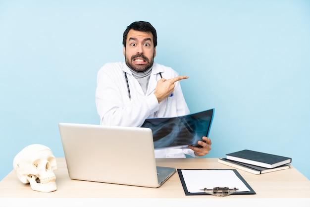 Traumatologista profissional no local de trabalho assustado e apontando para o lado