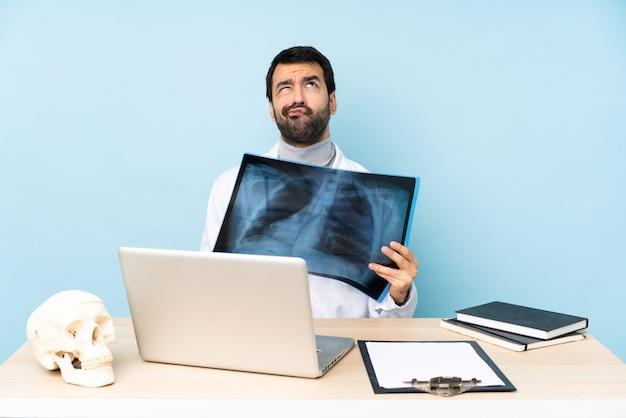 Traumatologista profissional no local de trabalho e olhando para cima
