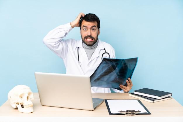 Traumatologista profissional no local de trabalho frustrado e leva as mãos na cabeça