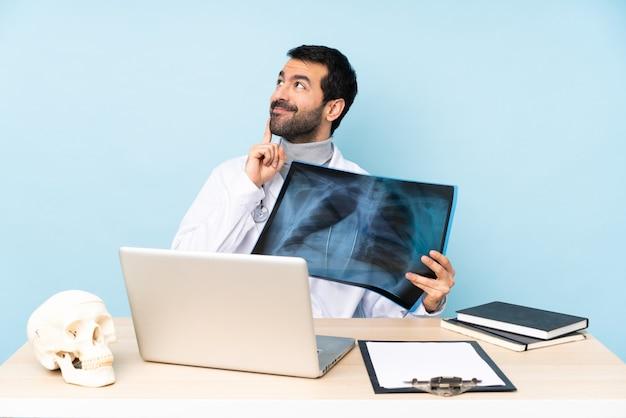 Traumatologista profissional no local de trabalho, pensando uma idéia enquanto olha para cima