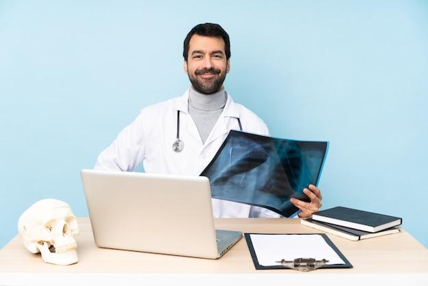 Traumatologista profissional no local de trabalho, posando com os braços no quadril e sorrindo