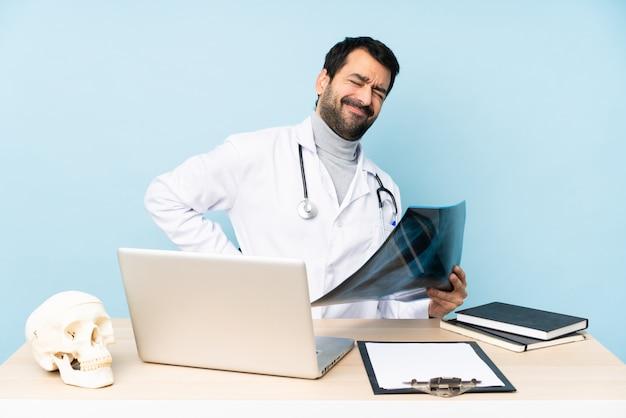 Traumatologista profissional no local de trabalho que sofre de dores nas costas por ter feito um esforço