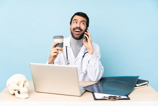 Traumatologista profissional no local de trabalho, segurando o café para levar e um celular