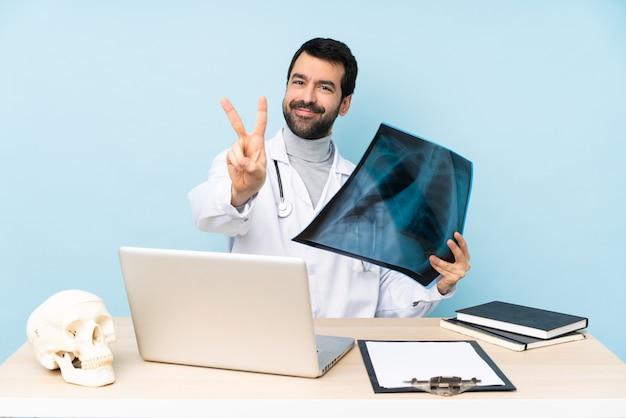 Traumatologista profissional no local de trabalho sorrindo e mostrando sinal de vitória