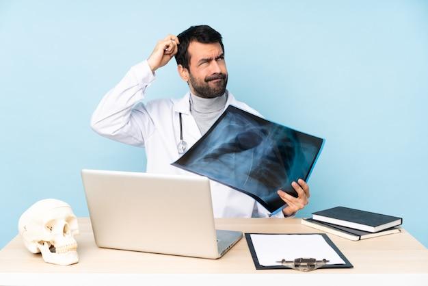 Traumatologista profissional no local de trabalho, tendo dúvidas ao coçar a cabeça