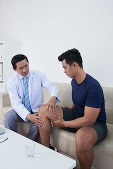 Traumatologista que apalpa o joelho do paciente