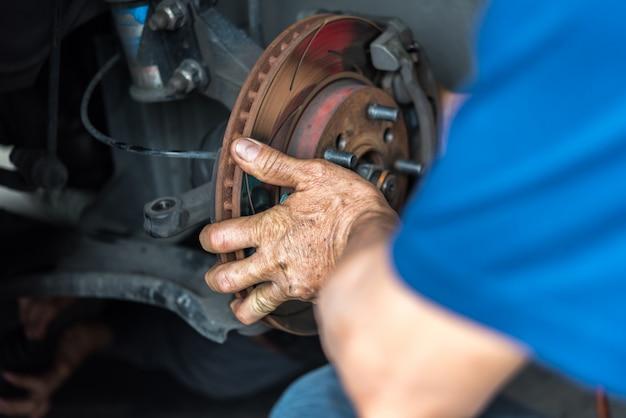 Travão de disco e pastilhas de freio de amianto na garagem do carro