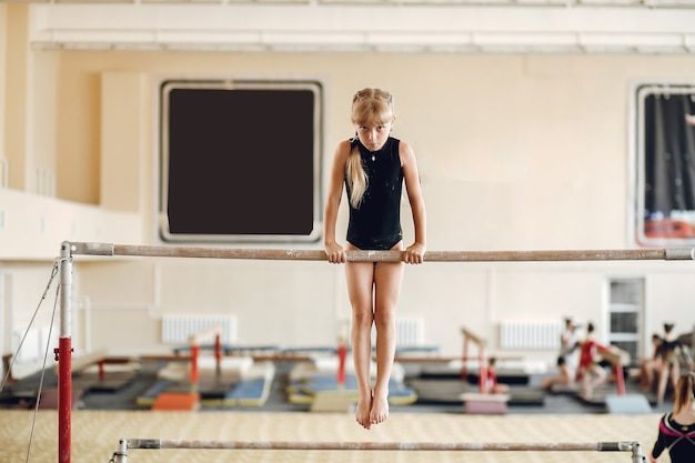 Trave de equilíbrio de ginástica infantil. atleta de ginasta durante uma barra horizontal de exercícios em competições de ginástica. Foto gratuita
