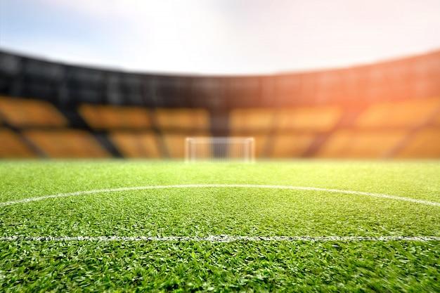 Trave de grama verde e futebol com tribuna